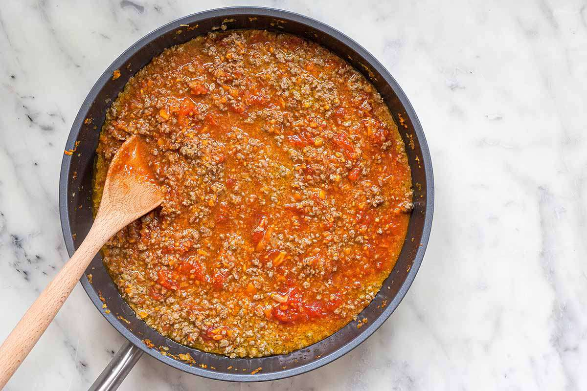 A homemade meaty bolognese sauce in a skillet on a marble countertop with a wooden spoon.