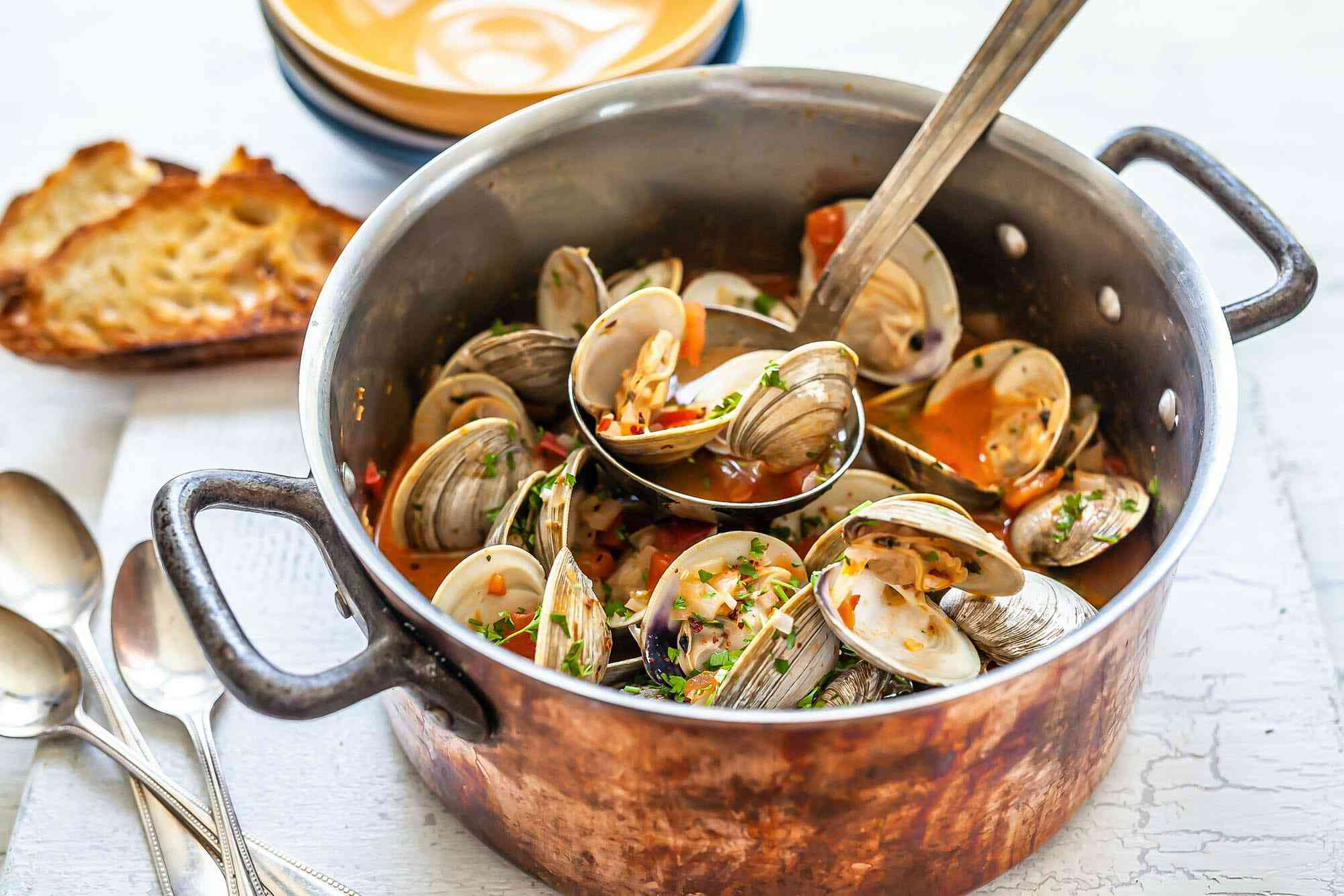 Stockpot of spanish clams and chorizo with a full ladle of the clams resting on top of the pot. Grilled bread, spoons and bowls are around the pot.