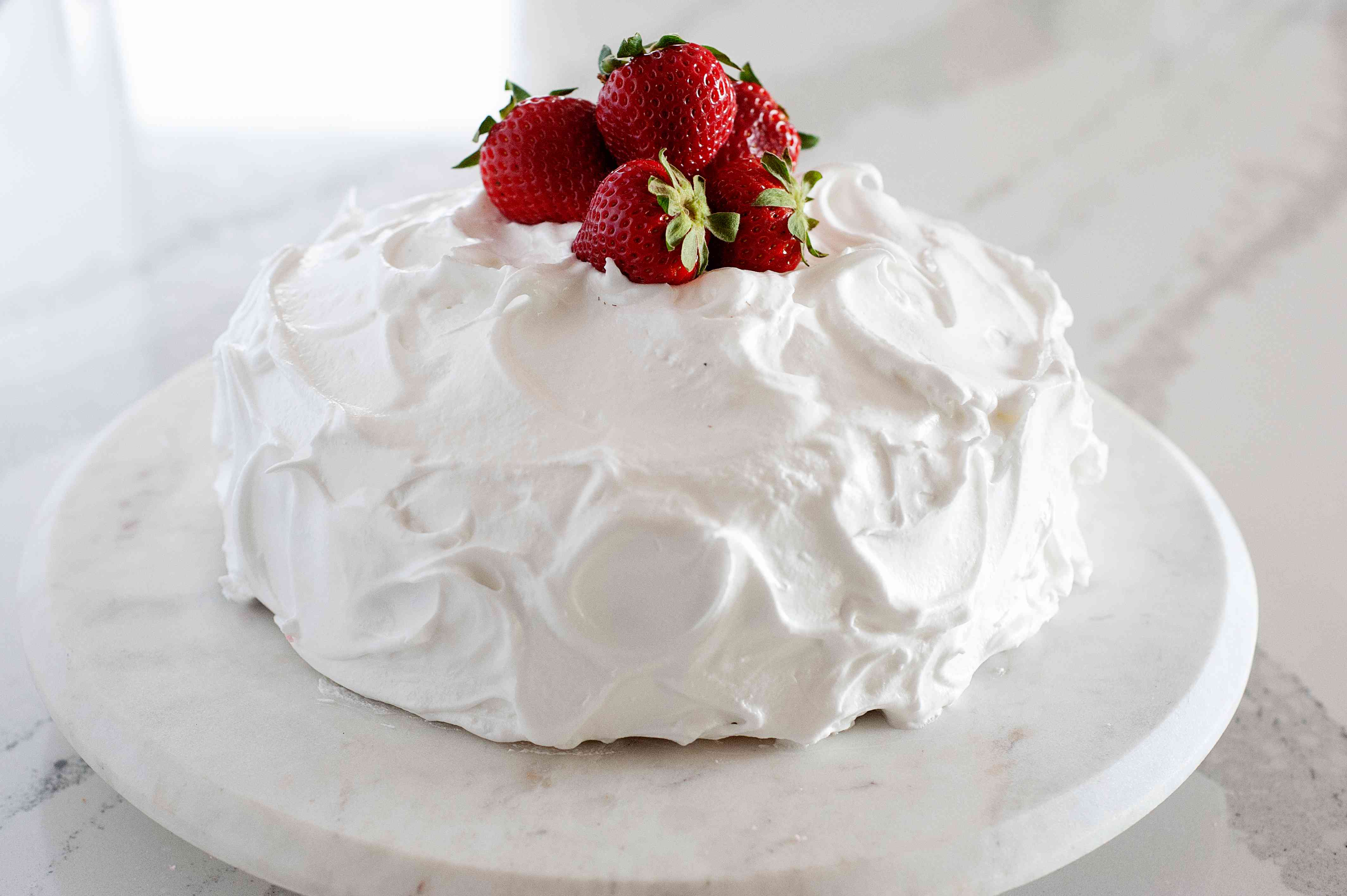 Side view of Homemade Strawberry Layer Cake on a cake stand and topped with strawberries.