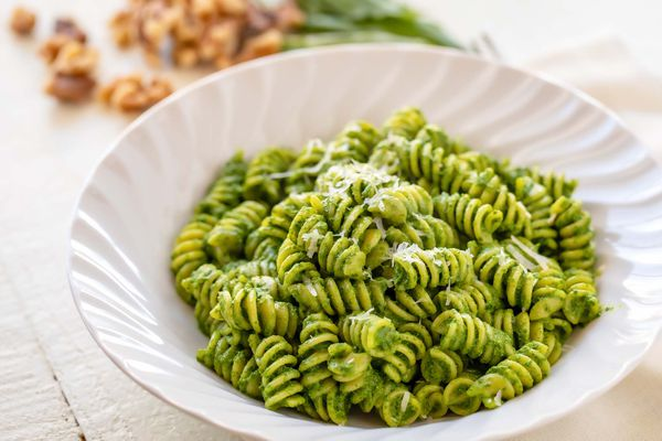 Horizontal view of a white bowl with rotini and kale pesto inside. Walnuts and basil are in the background.