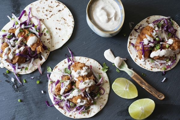 Best Fish Tacos with slaw and crema - fish tacos on grey slate with crema and lime