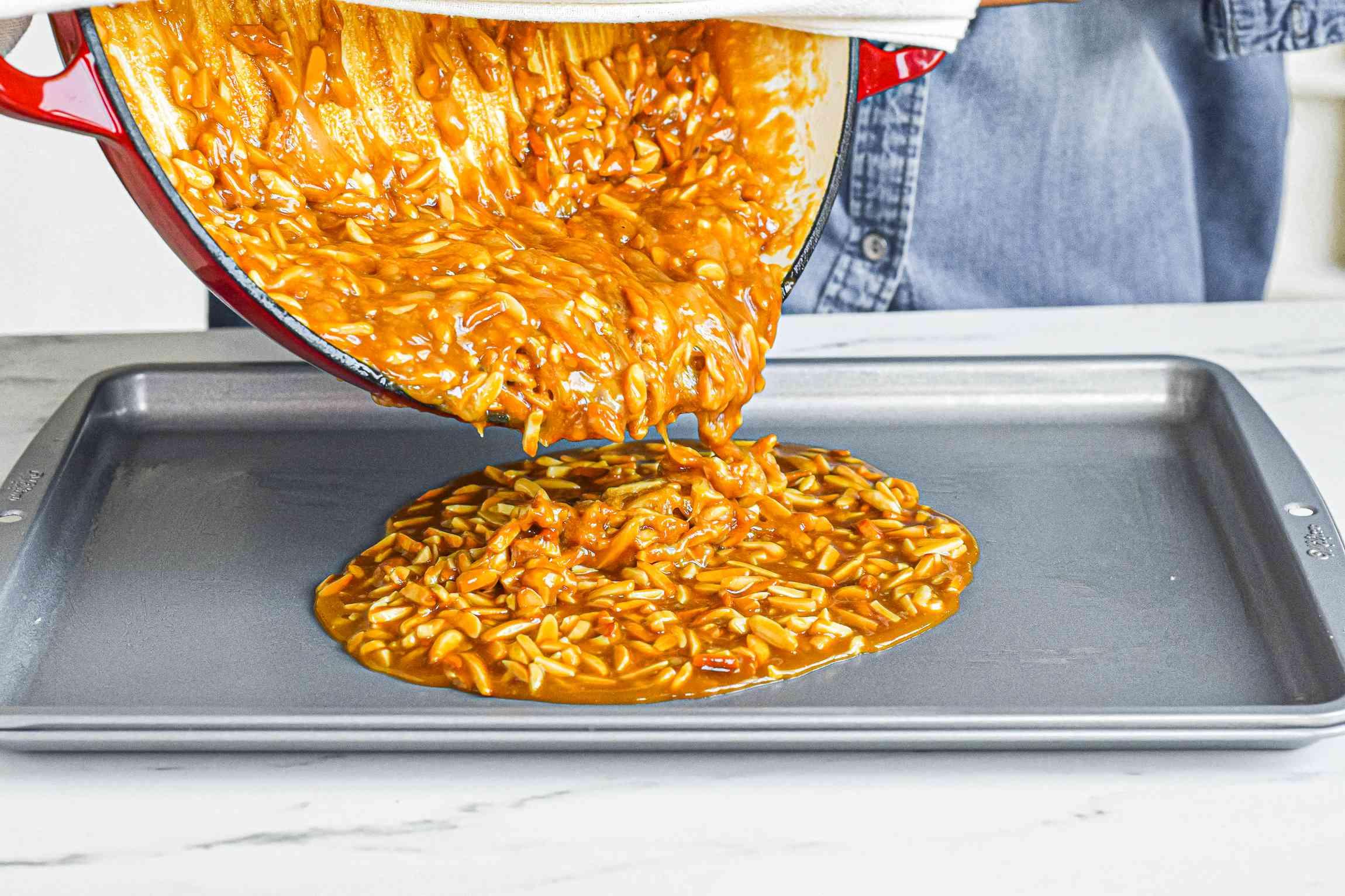 Pouring almond roca onto a baking sheet.