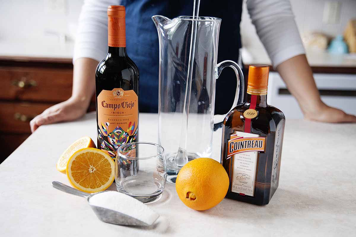 Homemade Sangria Recipe - orange slices in a pitcher of sangria on a silver tray with two poured glasses of sangria