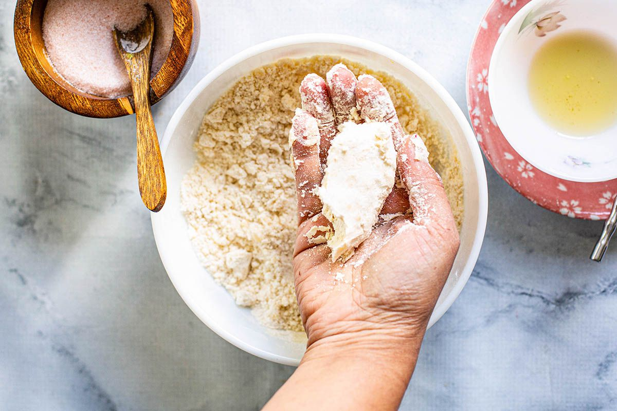 Woman's hand mixing Ingredients to make dough and grabing a fistful of it in her hands.