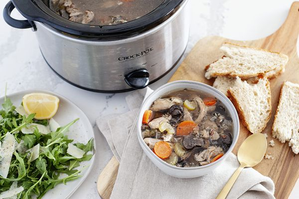 Easy Chicken and Rice Soup in a bowl with bread and salad nearby. A slow cooker is behind the bowl.