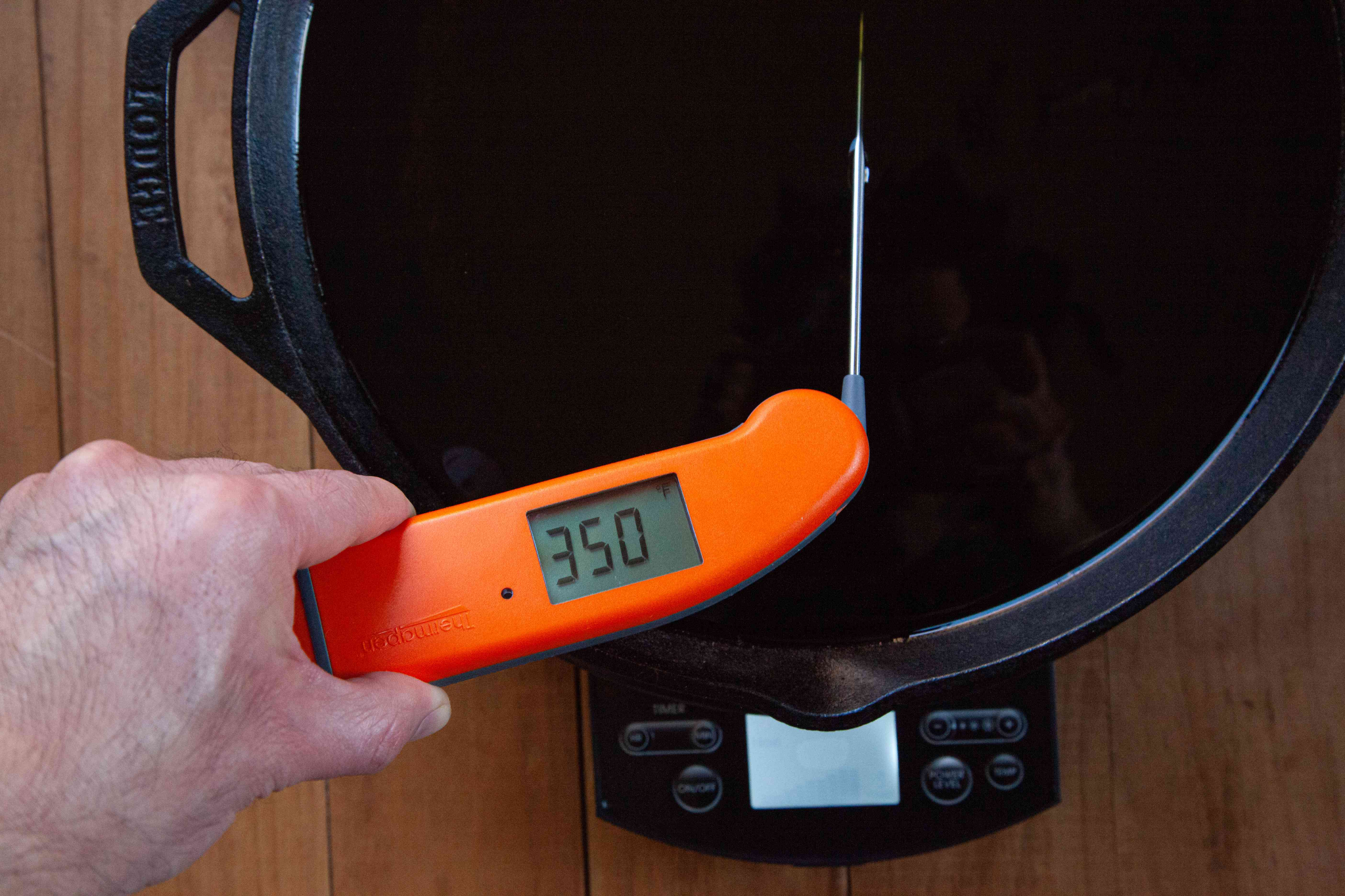 An instant read thermometer showing the temperature of frying oil for Nashville-style hot chicken.