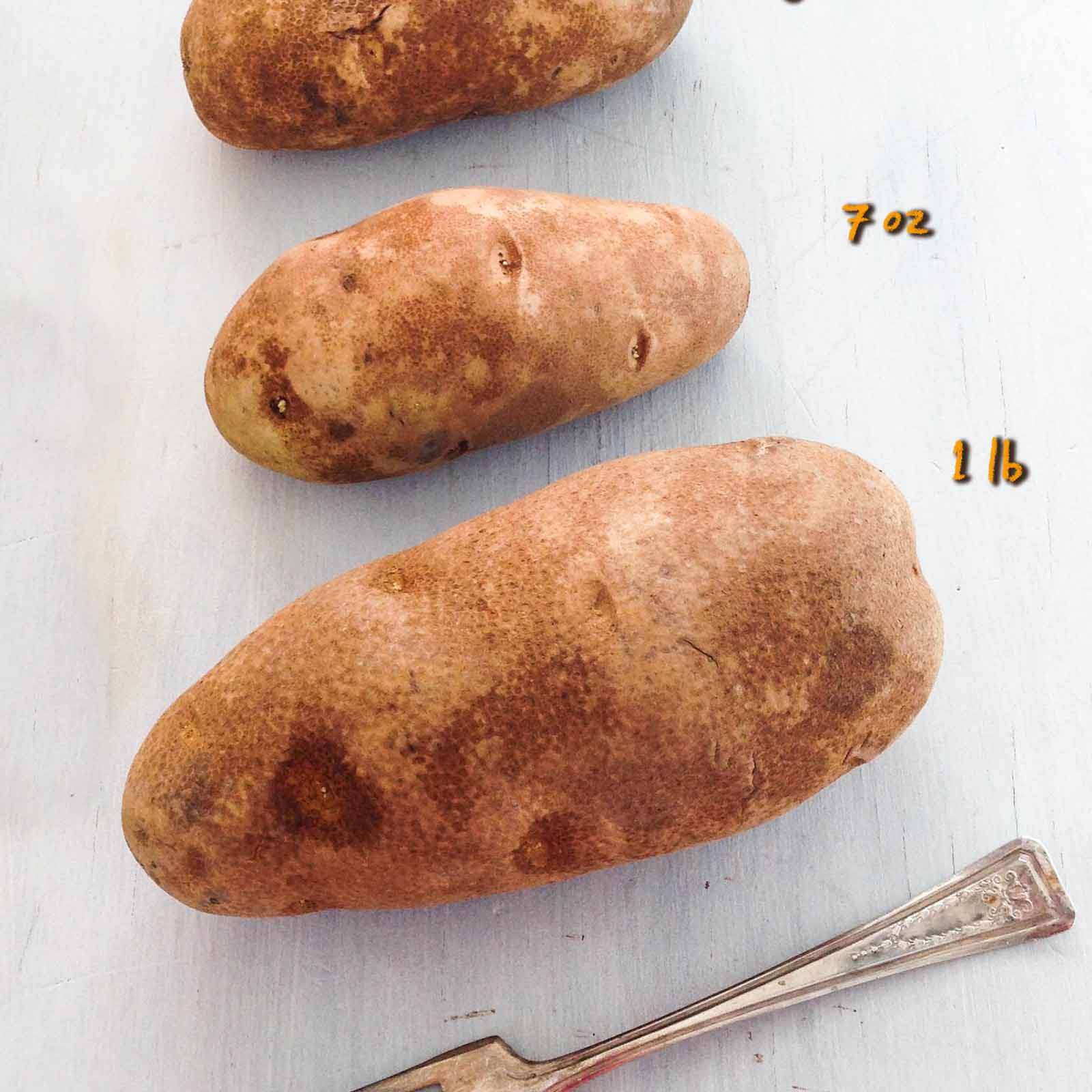 How to Make a Baked Potato in the Oven - potatoes lined up showing sizes