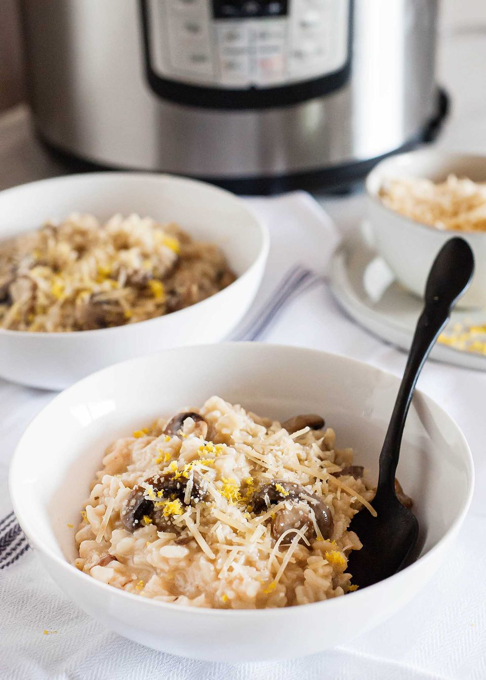 Insta Pot Mushroom Risotto -- white bowls filed creamy mushroom risotto in front of an Instant Pot