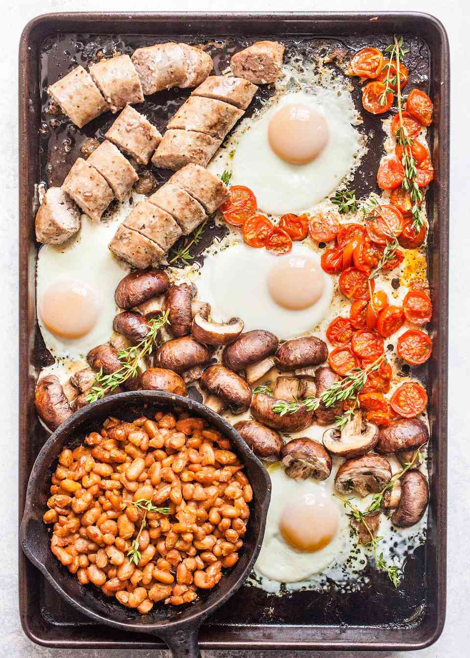 English Breakfast all on one sheet pan, with a pot of beans, cracked eggs, roasted tomatoes and potatoes, and sausages