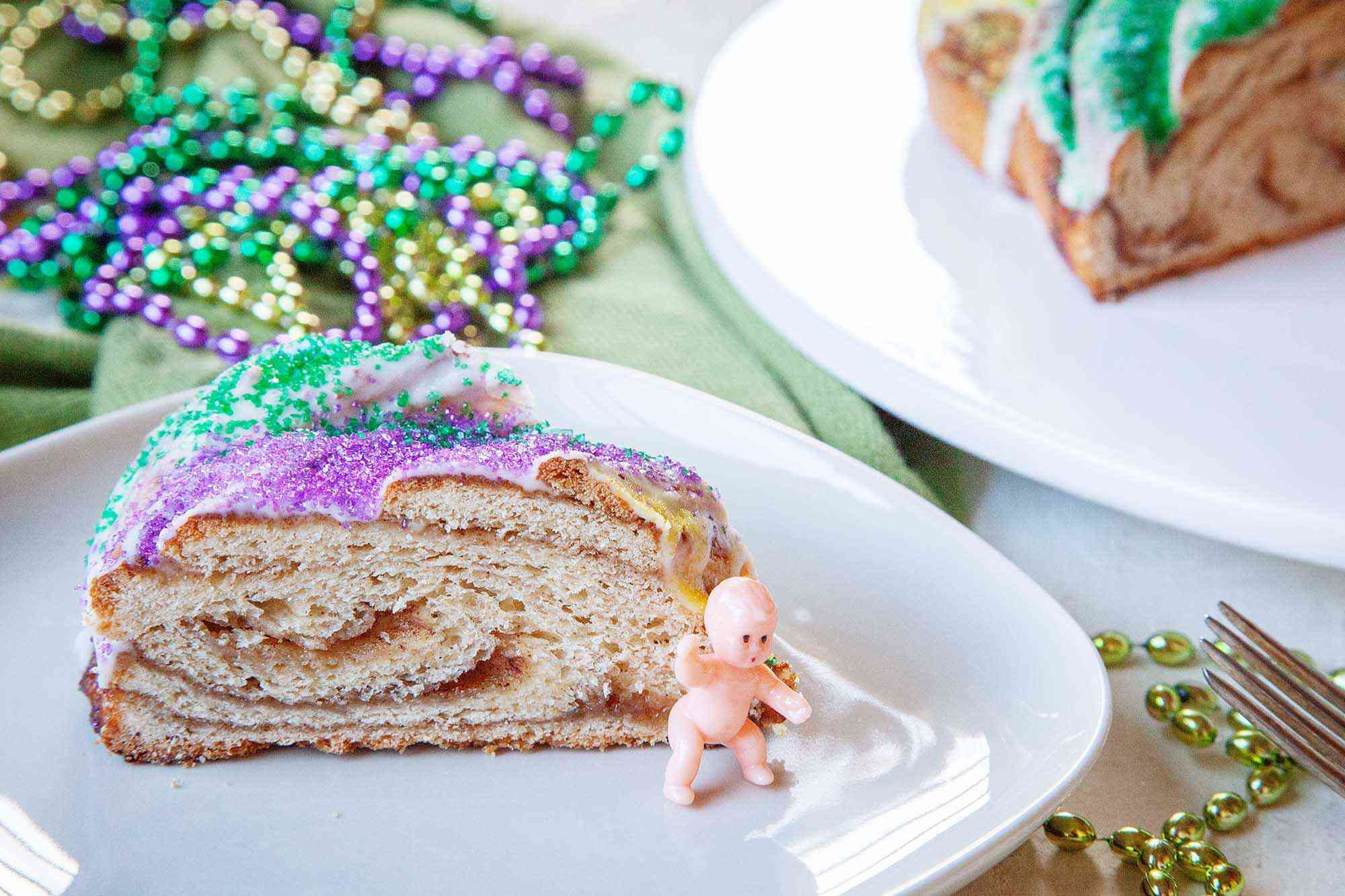Horizontal view of a slice of homemade king cake with a small baby figurine on the plate. Mardi Gras beads and a partial view of the rest of the cake are in the background.