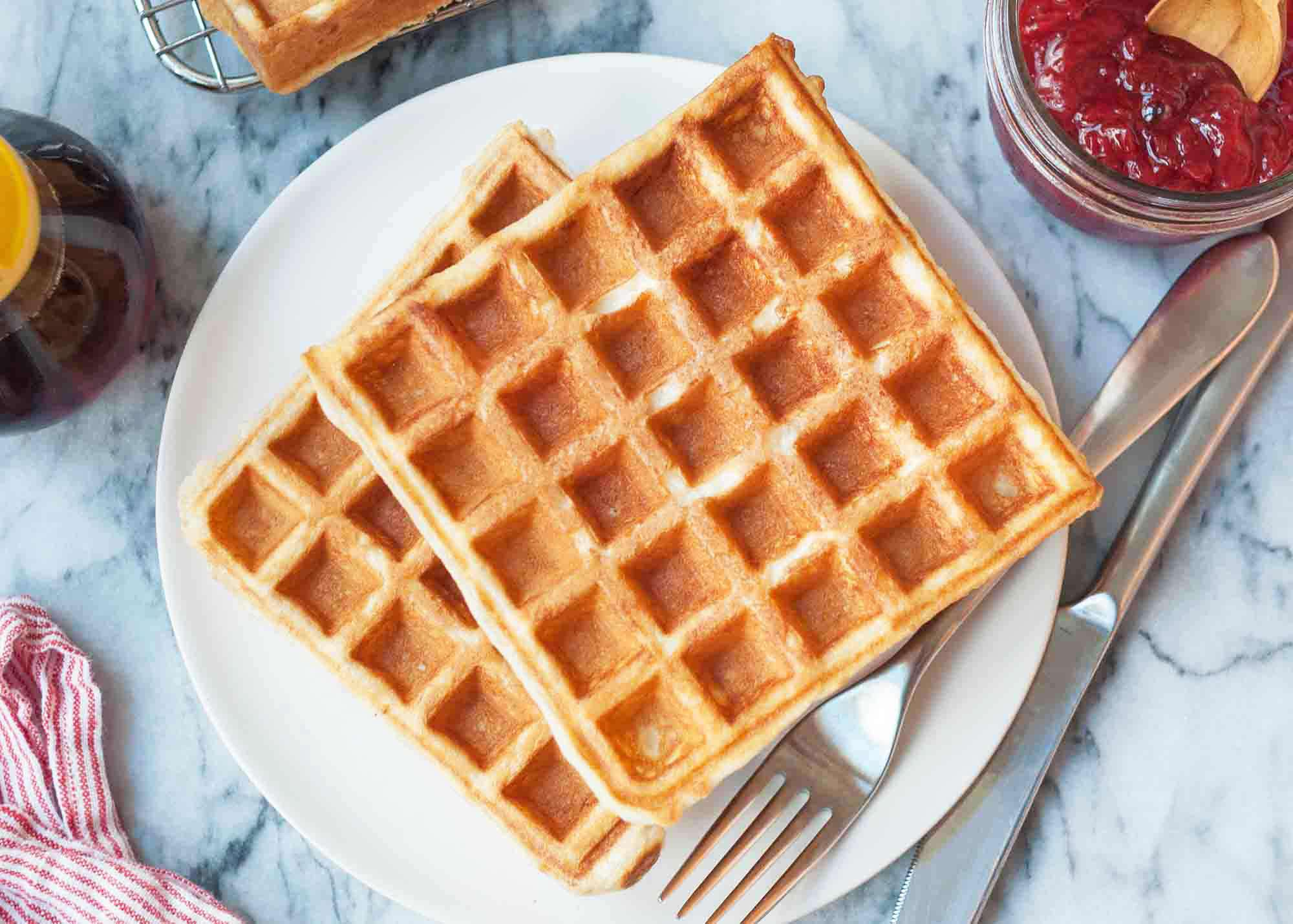 Easy waffle recipe served on a round plate with maple syrup
