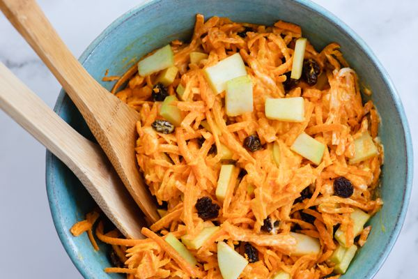 Classic Carrot Salad in a bowl with wooden serving spoons.