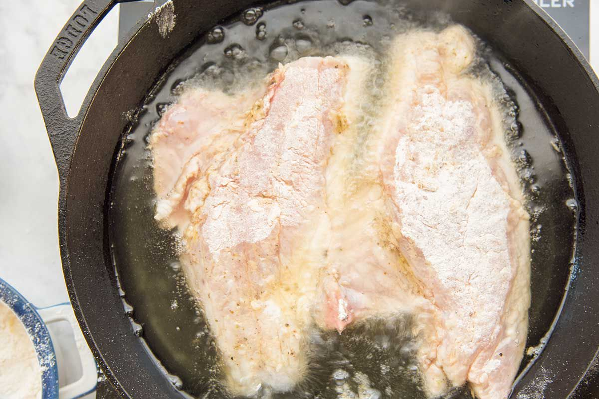 Raw red snapper fillets are side by side in a cast iron skillet. They are coated in flour and frying in oil in a cast iron skillet.