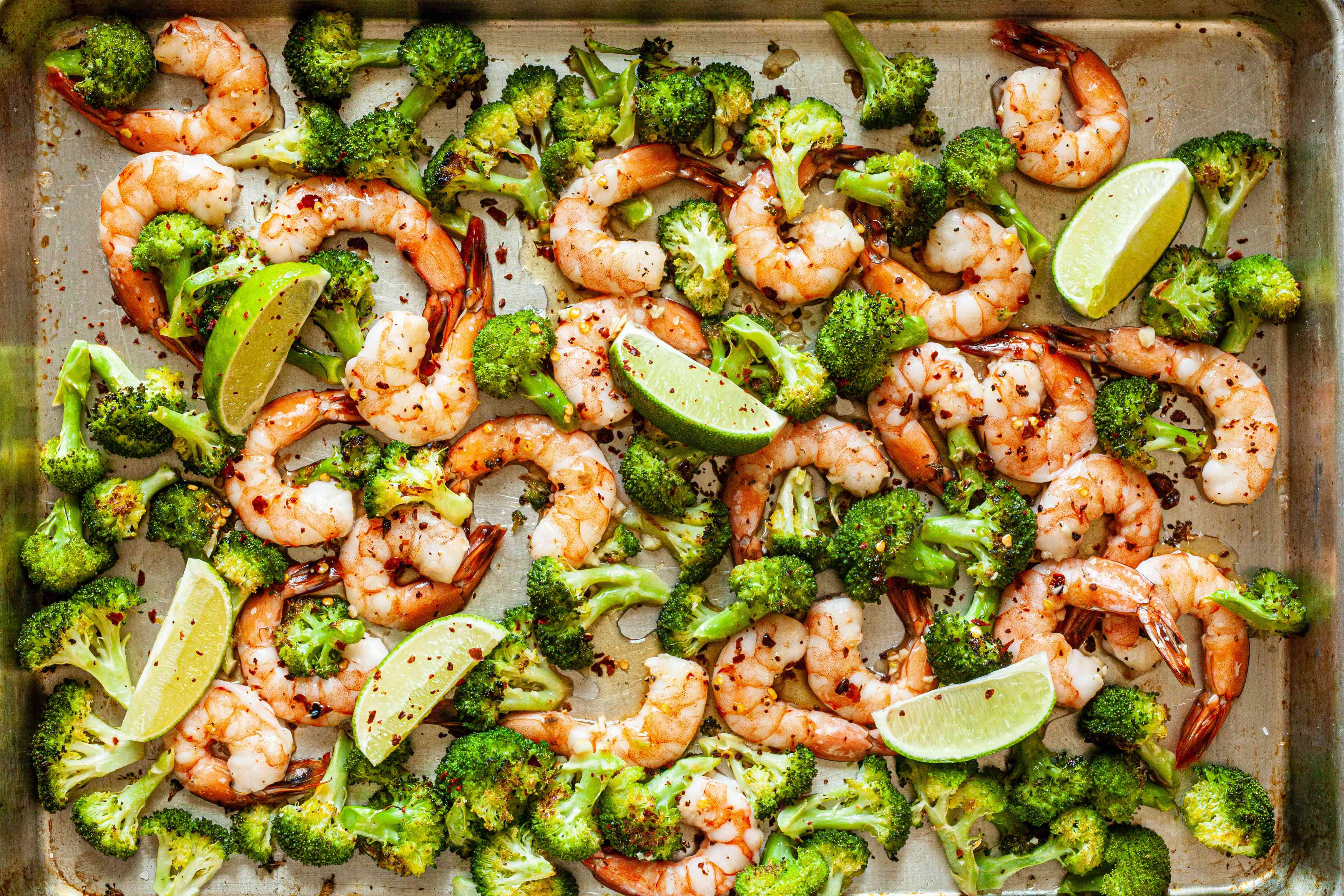Sheet Pan Hot Honey Roasted Shrimp and Broccoli on sheet pan with limes.