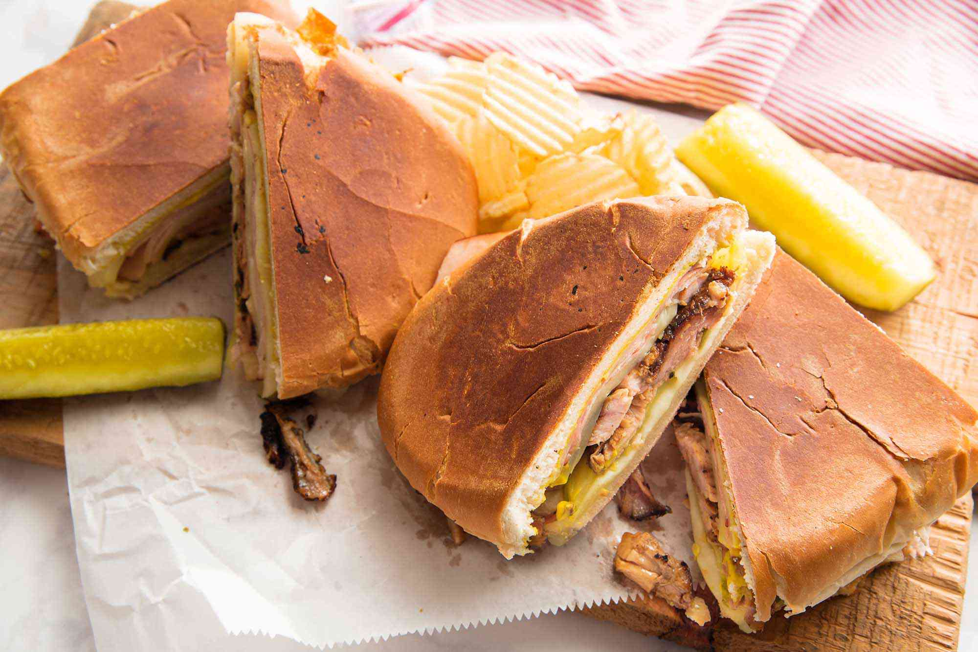A grilled cuban sandwich is cut into quarters and resting on top of parchment paper and cutting board. Shredded pork and pickles are visible inside the sandwich. Pickles are on either side of the sandwich and a pink striped dish cloth is in the left hand corner.