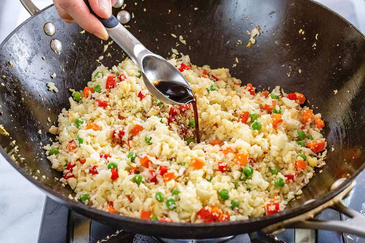 How to Make Cauliflower Fried Rice - adding brown sauce to - vegetable fried rice in wok