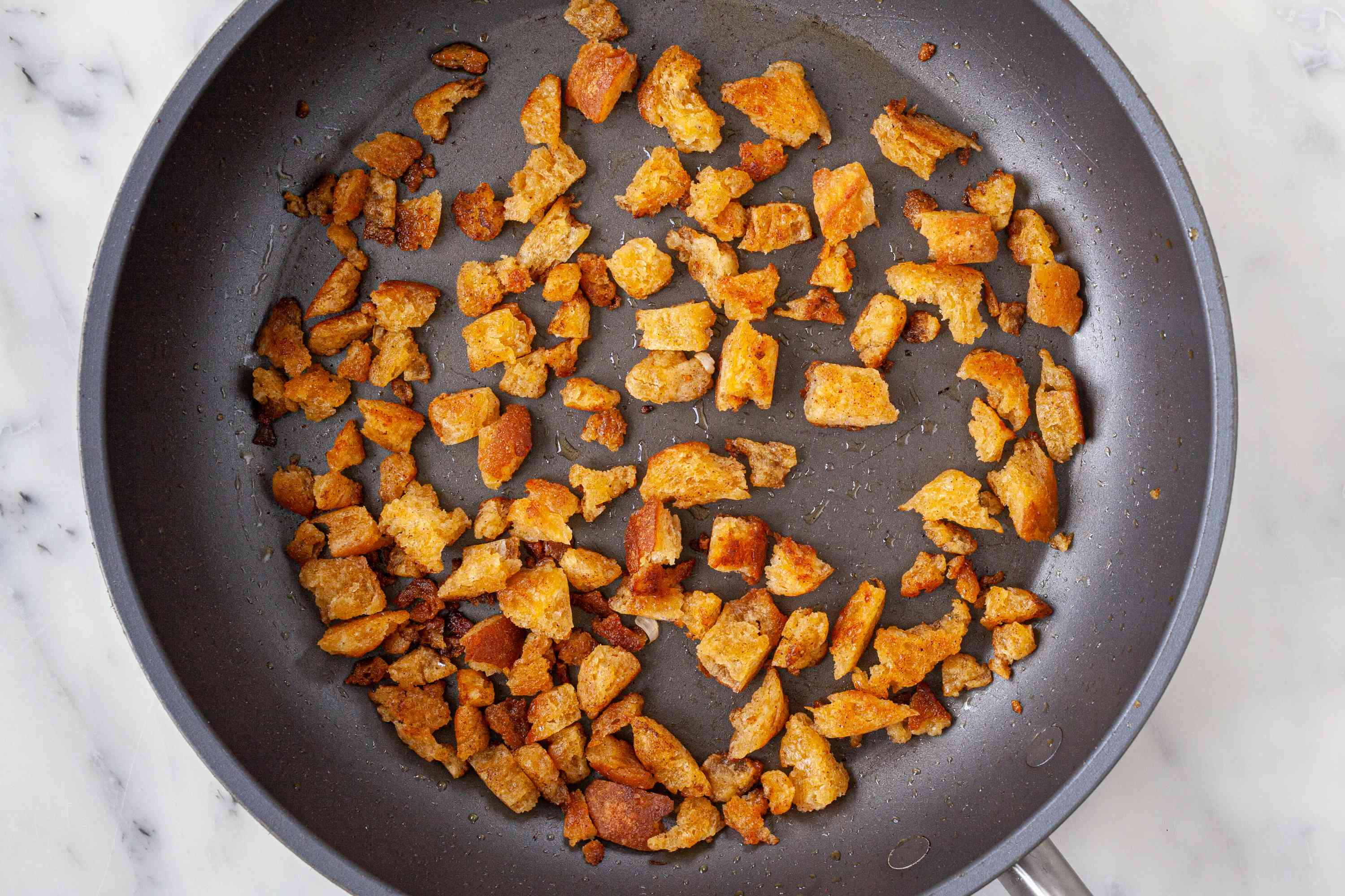 Frying cubed bread in a skillet for Spanish Style Migas with Asparagus, Chorizo, Bacon, and Eggs.
