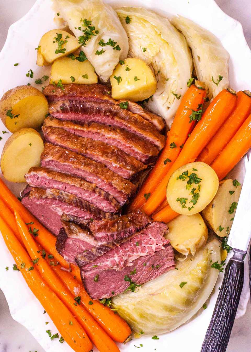 How to Boil Corned Beef and Cabbage - platter of sliced corned beef, carrots, potatoes, and cabbage sprinkled with herbs