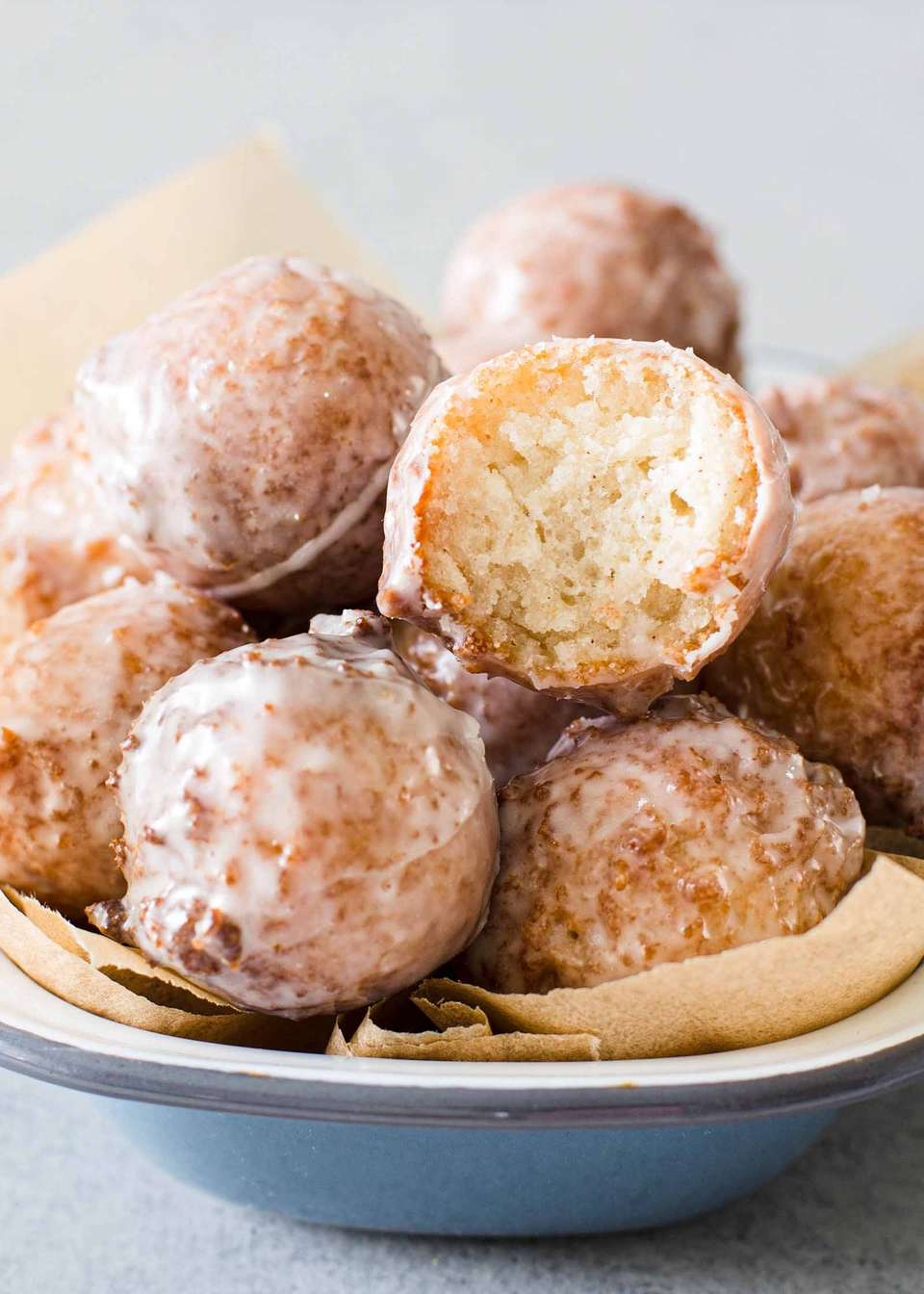 How to make these apple cider donut holes, which are piled up in a while bowl. The one on top has a bite taken out of it.