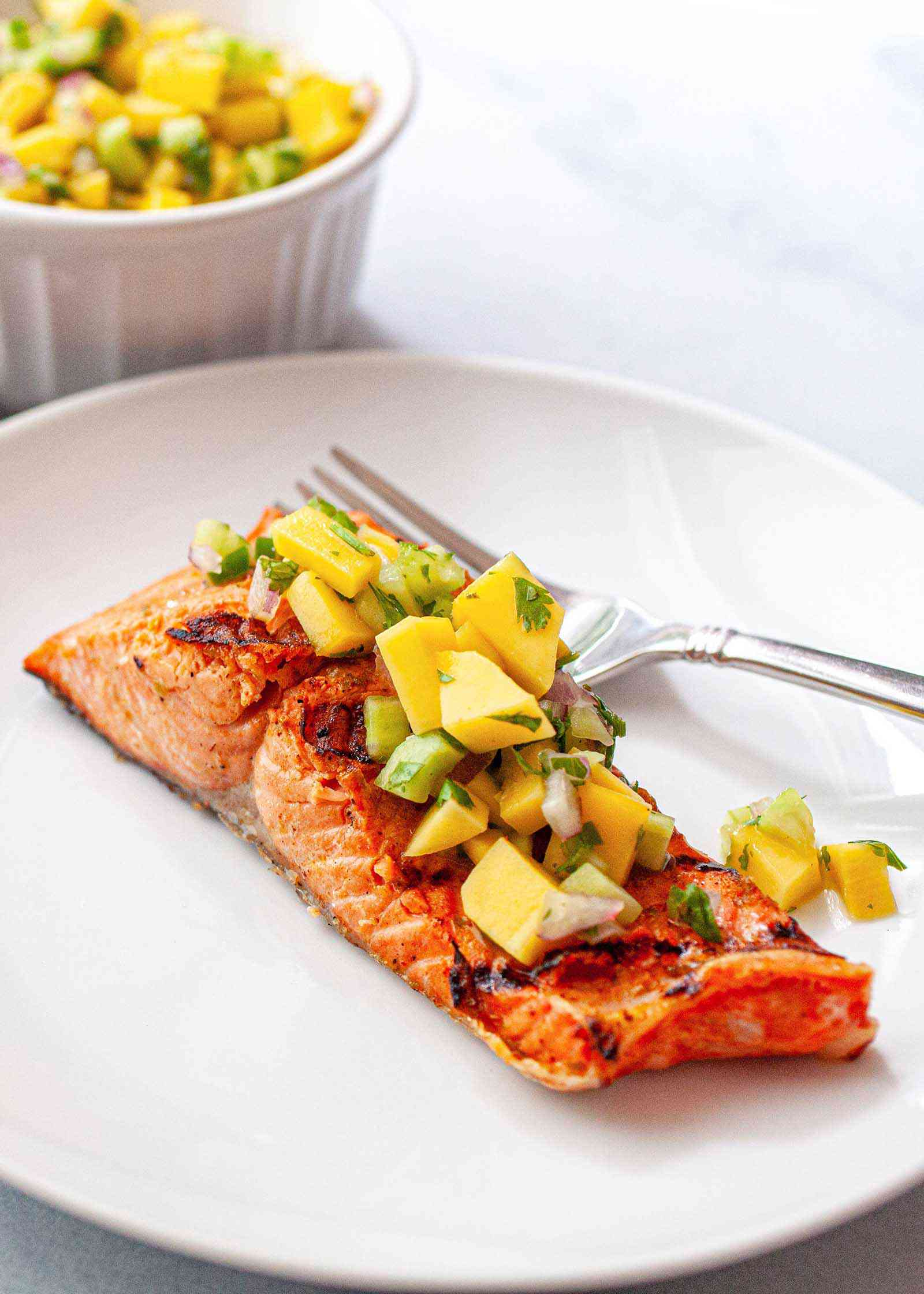 Grilled Salmon with Skin - grilled salmon portions on a plate with fresh salsa and a fork