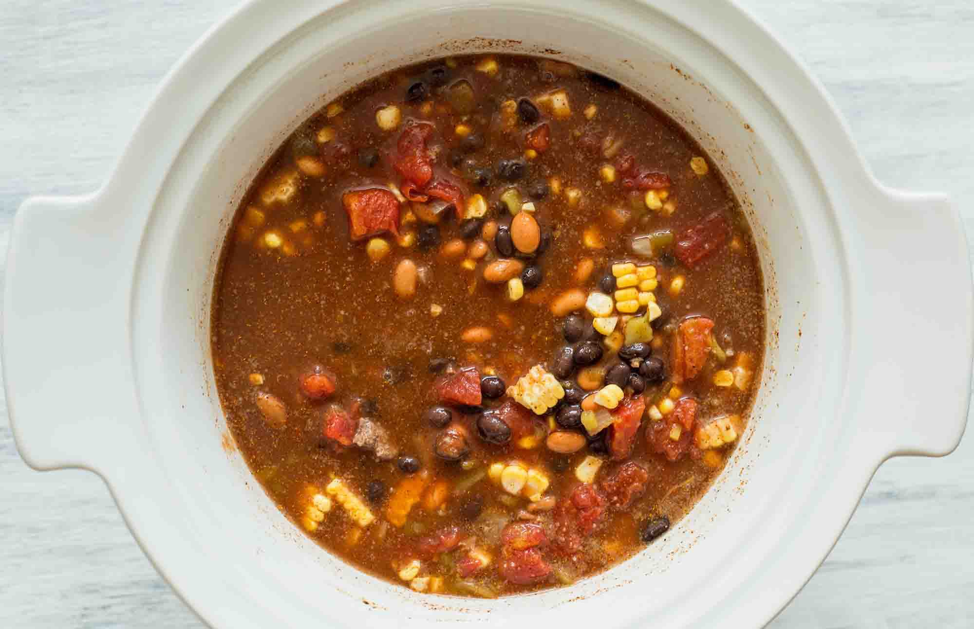 Stir together the ingredients for slow cooker taco soup in the crockpot insert