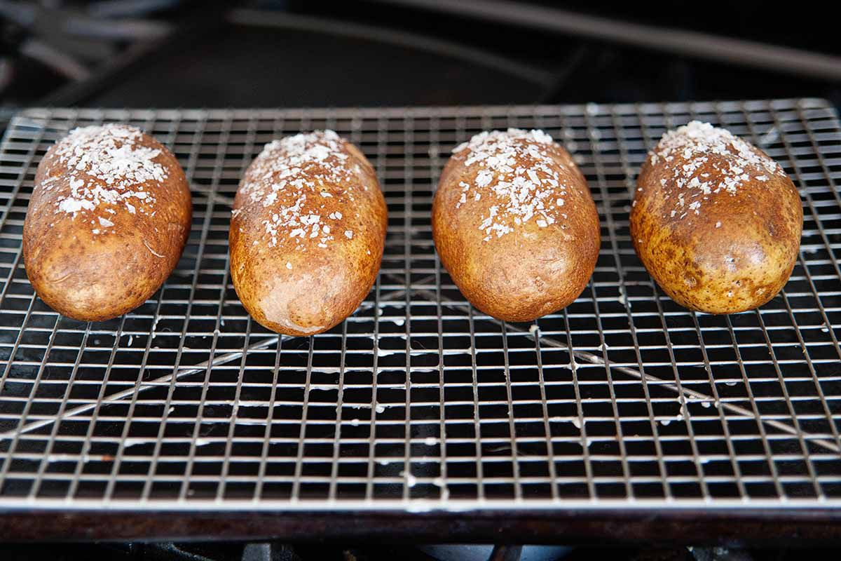 How to Make Baked Potatoes -- salted potatoes on a baking sheet in the oven