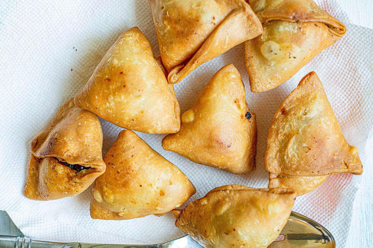 Triangles of the best vegetables samosas drainging on a plate with paper towels.
