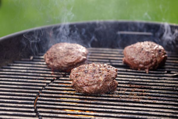 Burgers steaming on the grill