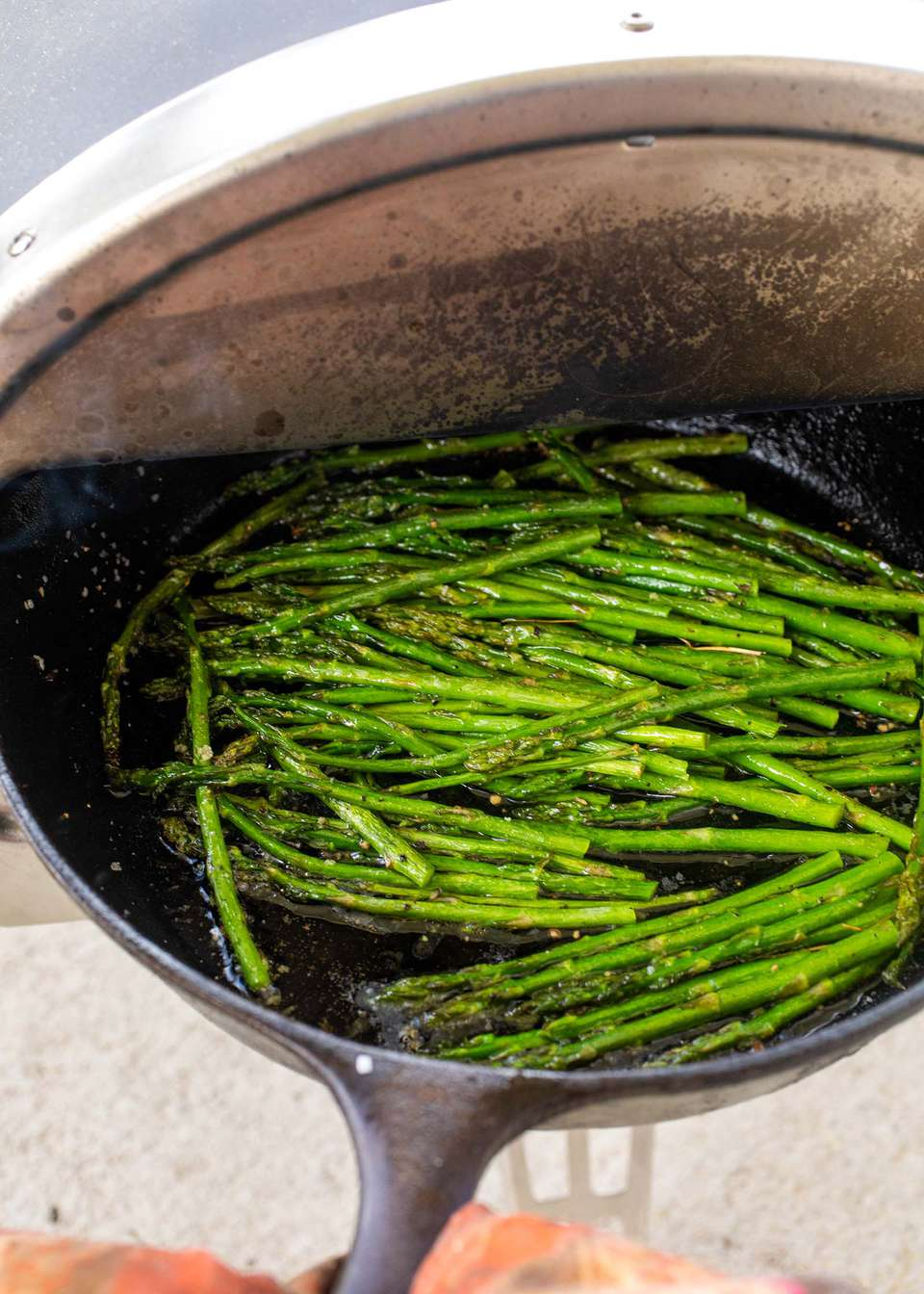 Cast iron skillet with asparagus being cooked inside a roccbox.