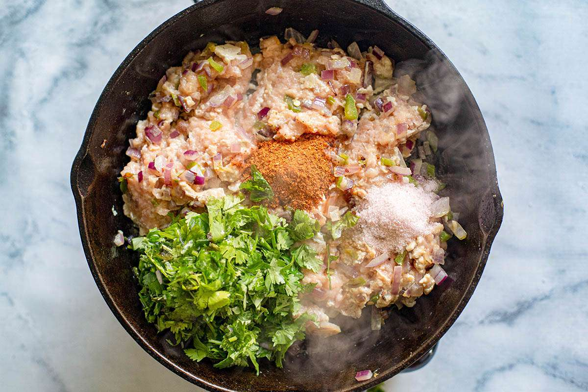 Ground chicken, onions, peppers, spices in a cast iron skillet to make Indian Chicken Tikka Masala Samosas