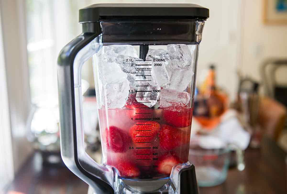 Ingredients for frozen strawberry daiquiris in a blender: strawberries, rum, simple syrup, lime juice, and ice
