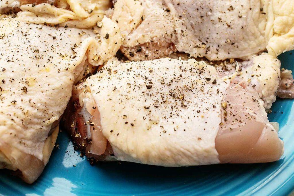 Season chicken thighs for cider-braised chicken thighs recipe