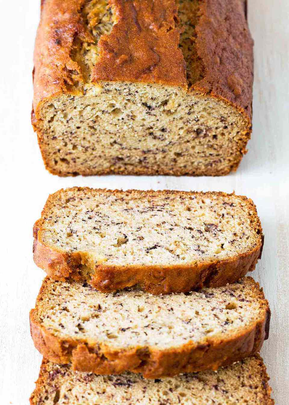 How to Thaw Banana Brea -- loaf of banana bread on white counter. Half the loaf is sliced.