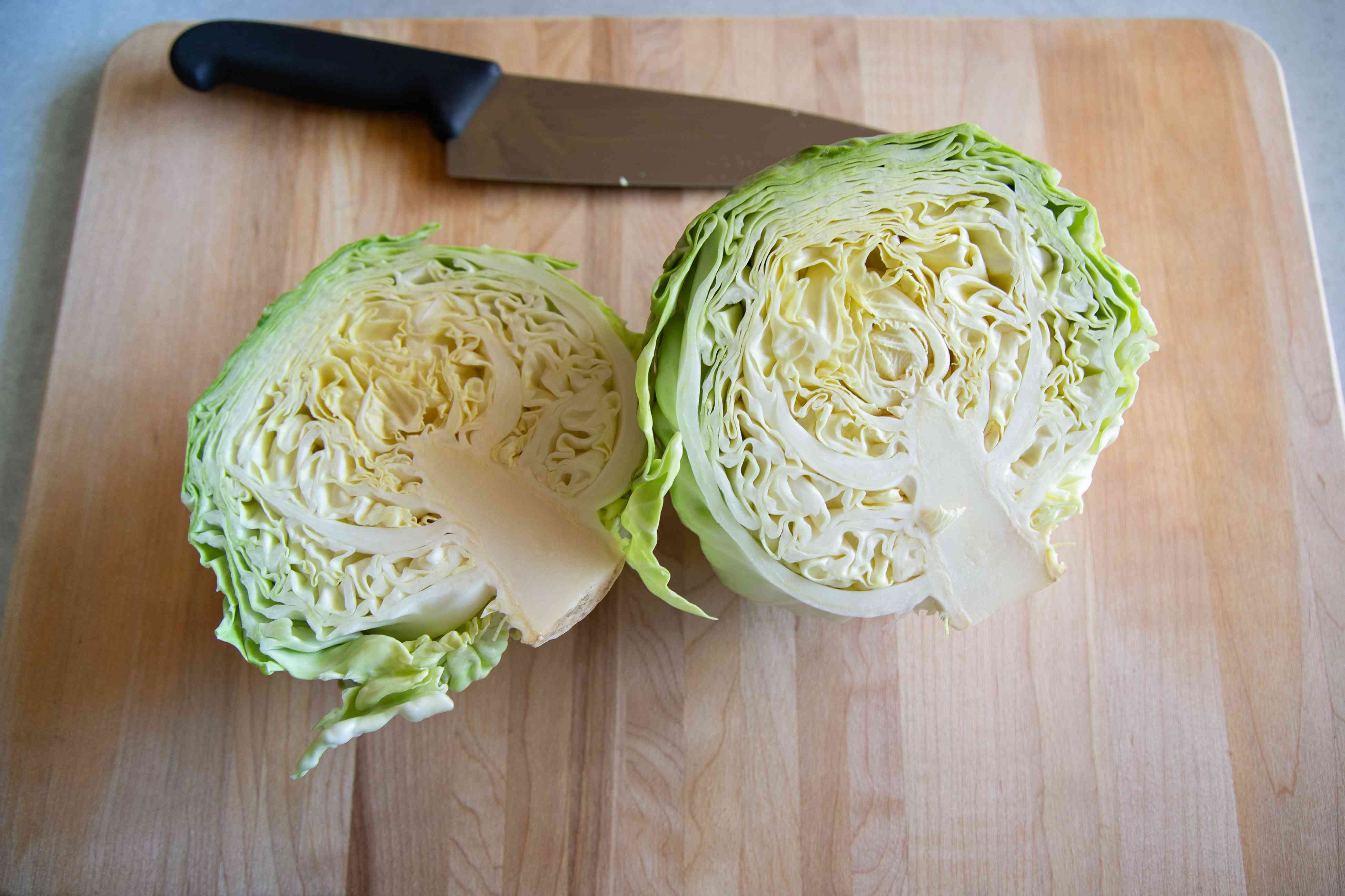 Chopping a head of cabbage in half on a cutting board.