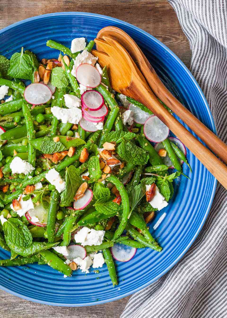 Easy Green Bean Recipe with Mint Pesto - blue bowl with a salad of green beans, radish, and wooden serving spoons on a wood table.
