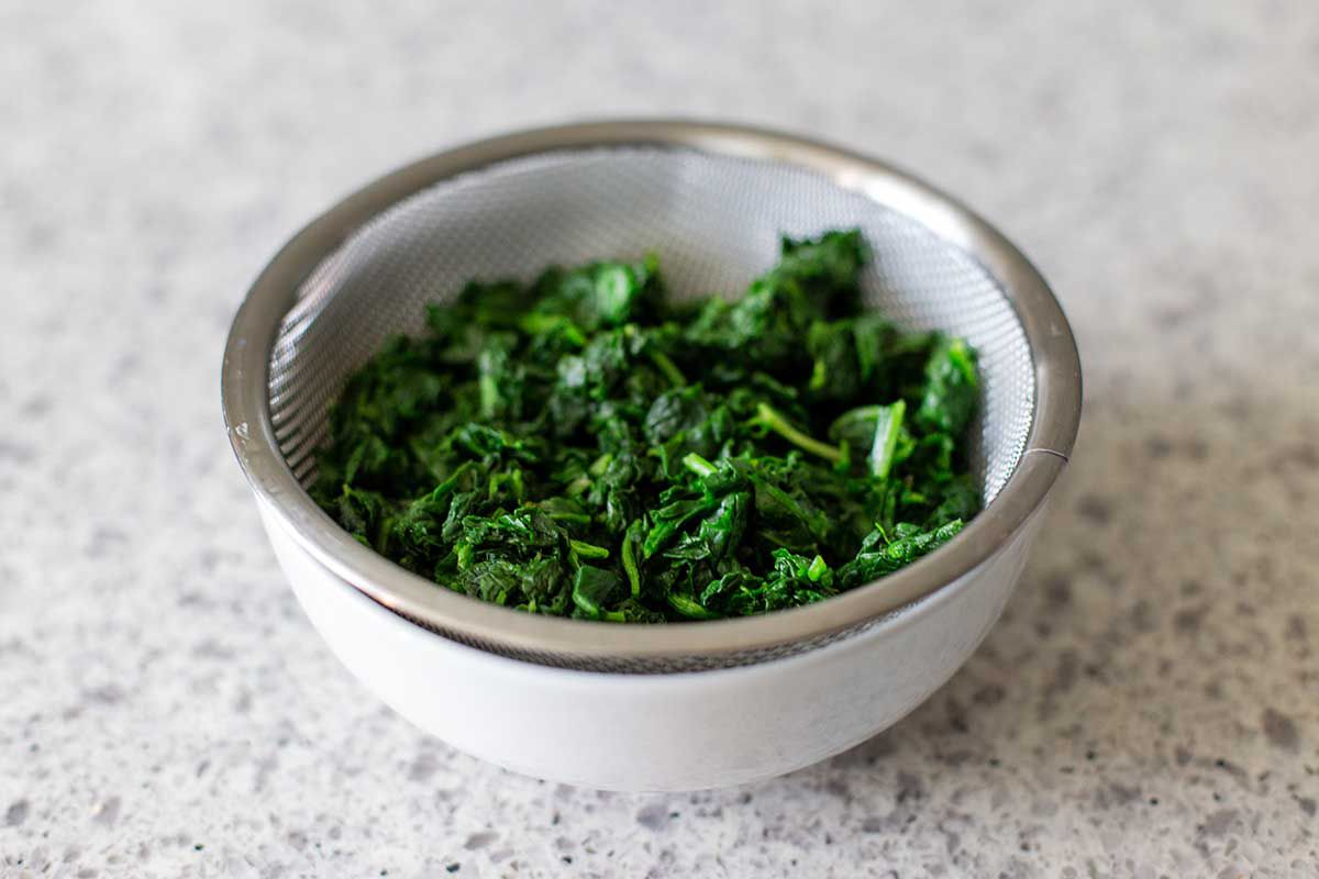 A small white bowl has a small sifter set inside with chopped frozen spinach draining.