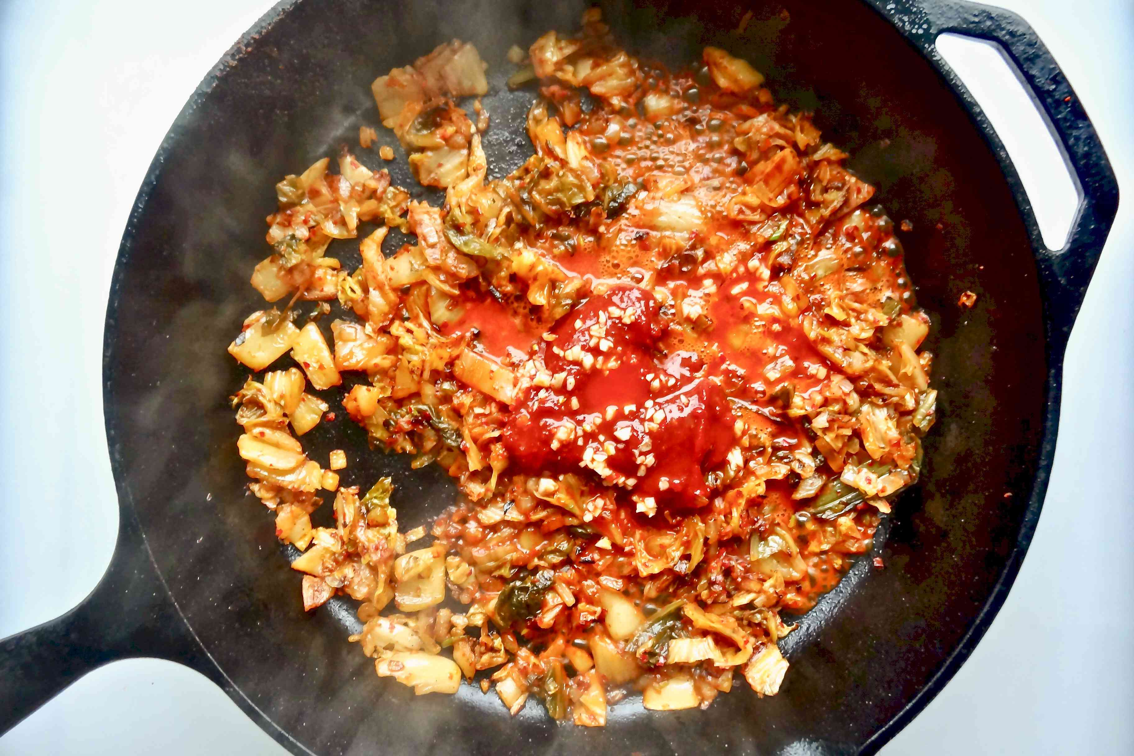 Adding the kimchi juice to the skillet for Korean fried rice with kimchi.
