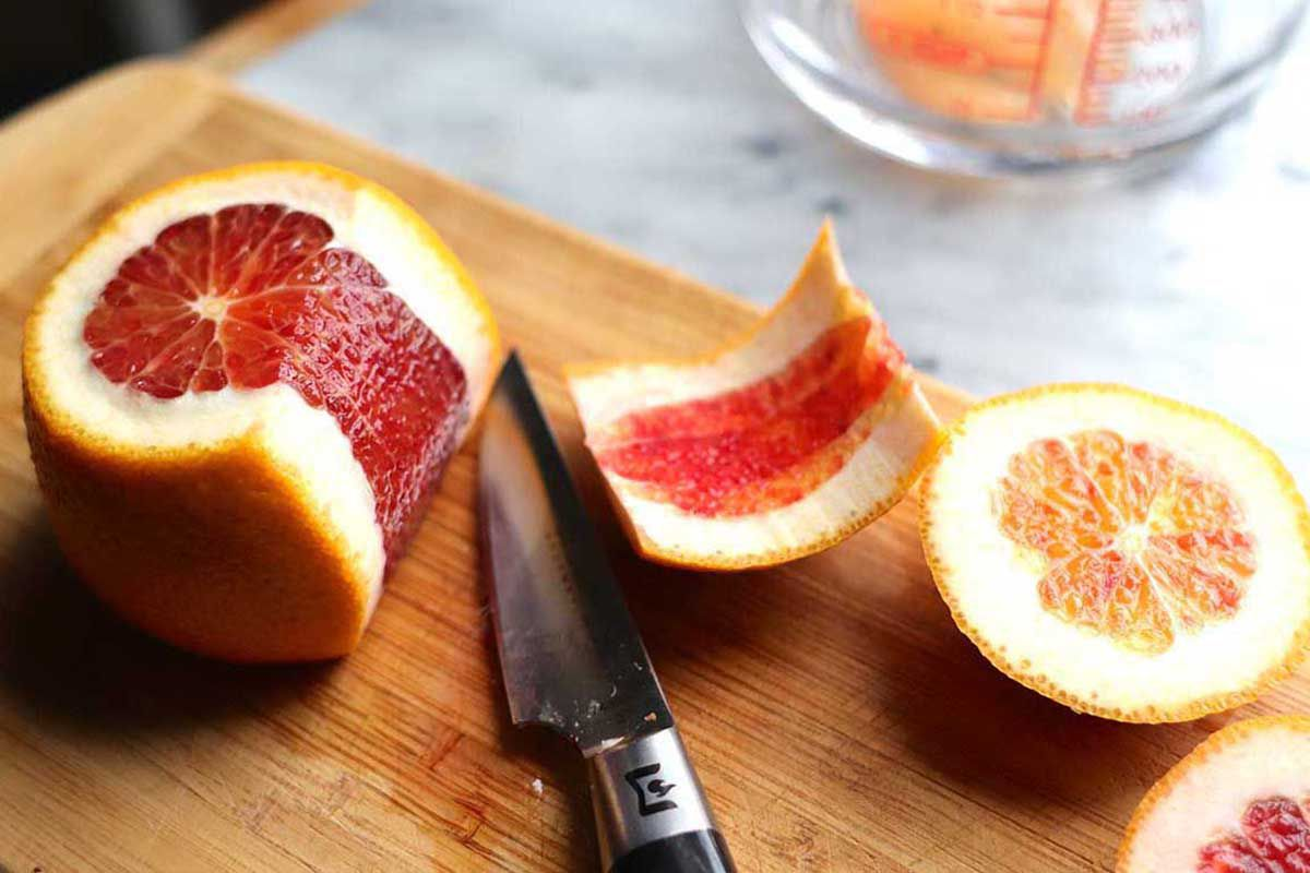 A side view of a blood orange with the top sliced off and the pith and peel partially cut off of it. The top and side peel is to the right of the knife.