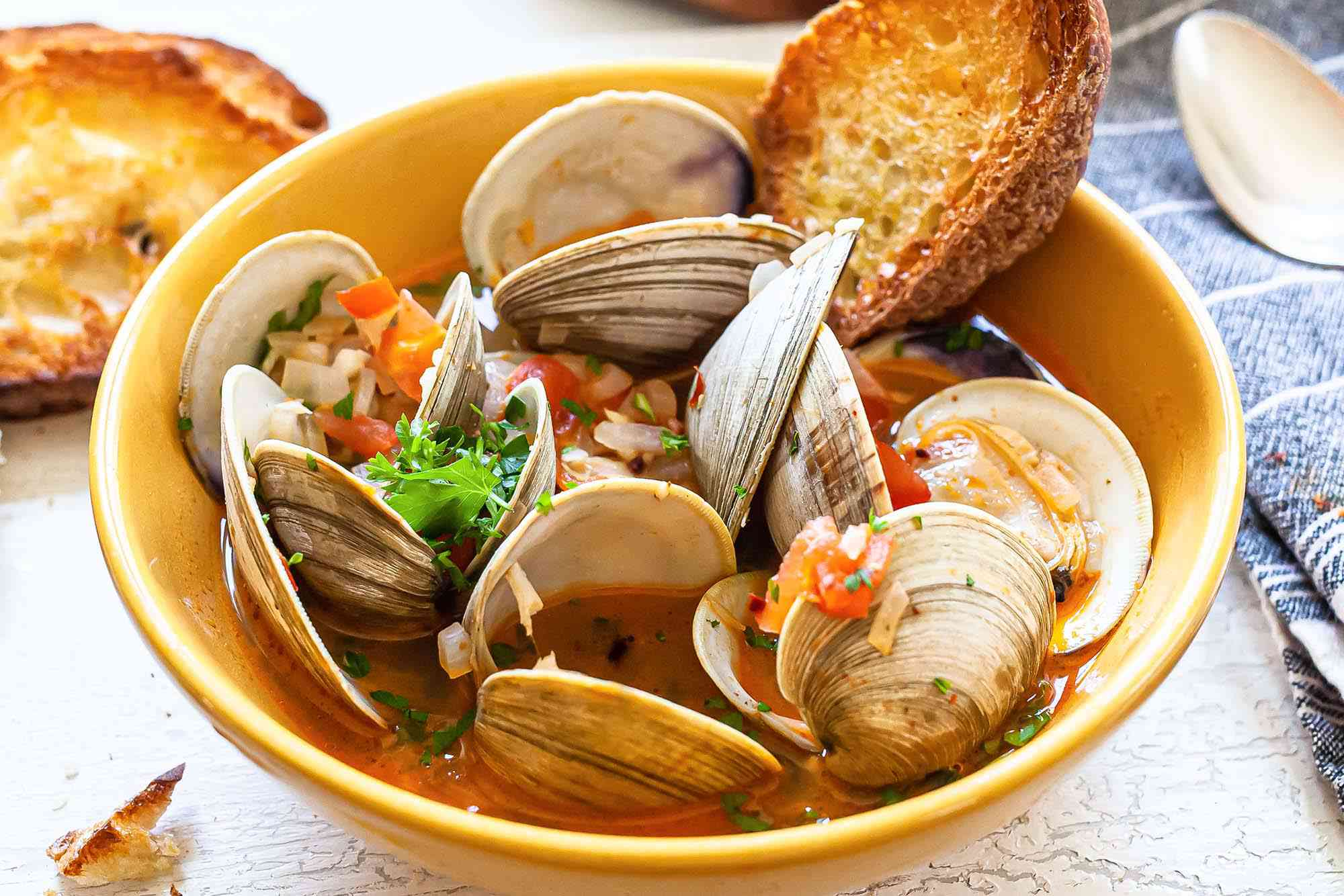 Yelllow bowl of chorizo clams with grilled bread with chopped tomatoes on top.