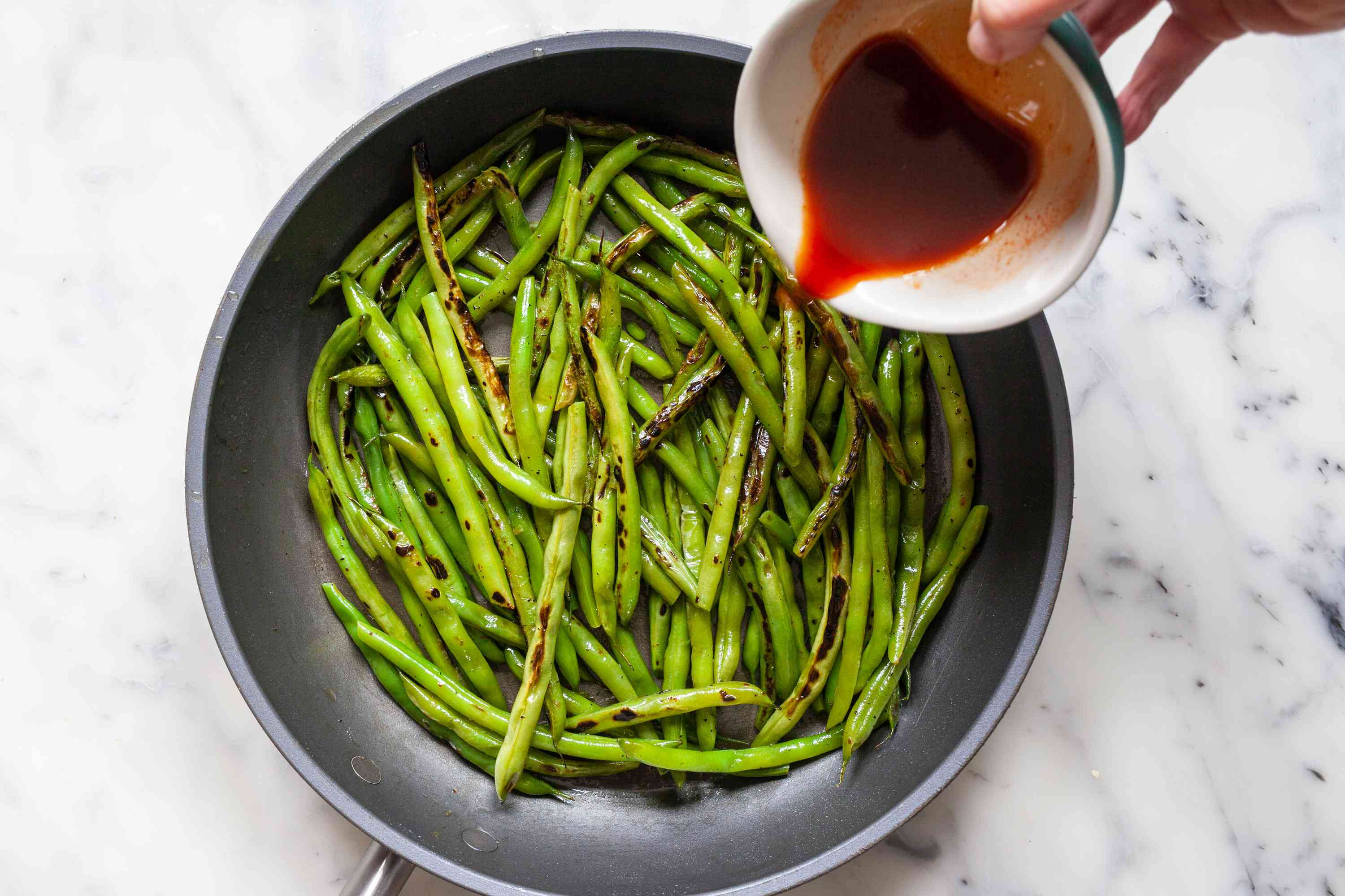 Adding the sauce for Spicy Korean Blistered Green Beans with Gochujang.