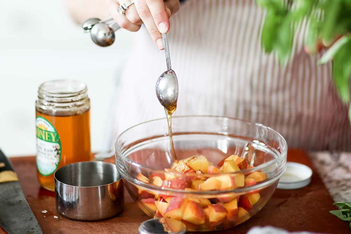Salad recipe with peaches, goat cheese, and pistachios toss the peaches with honey