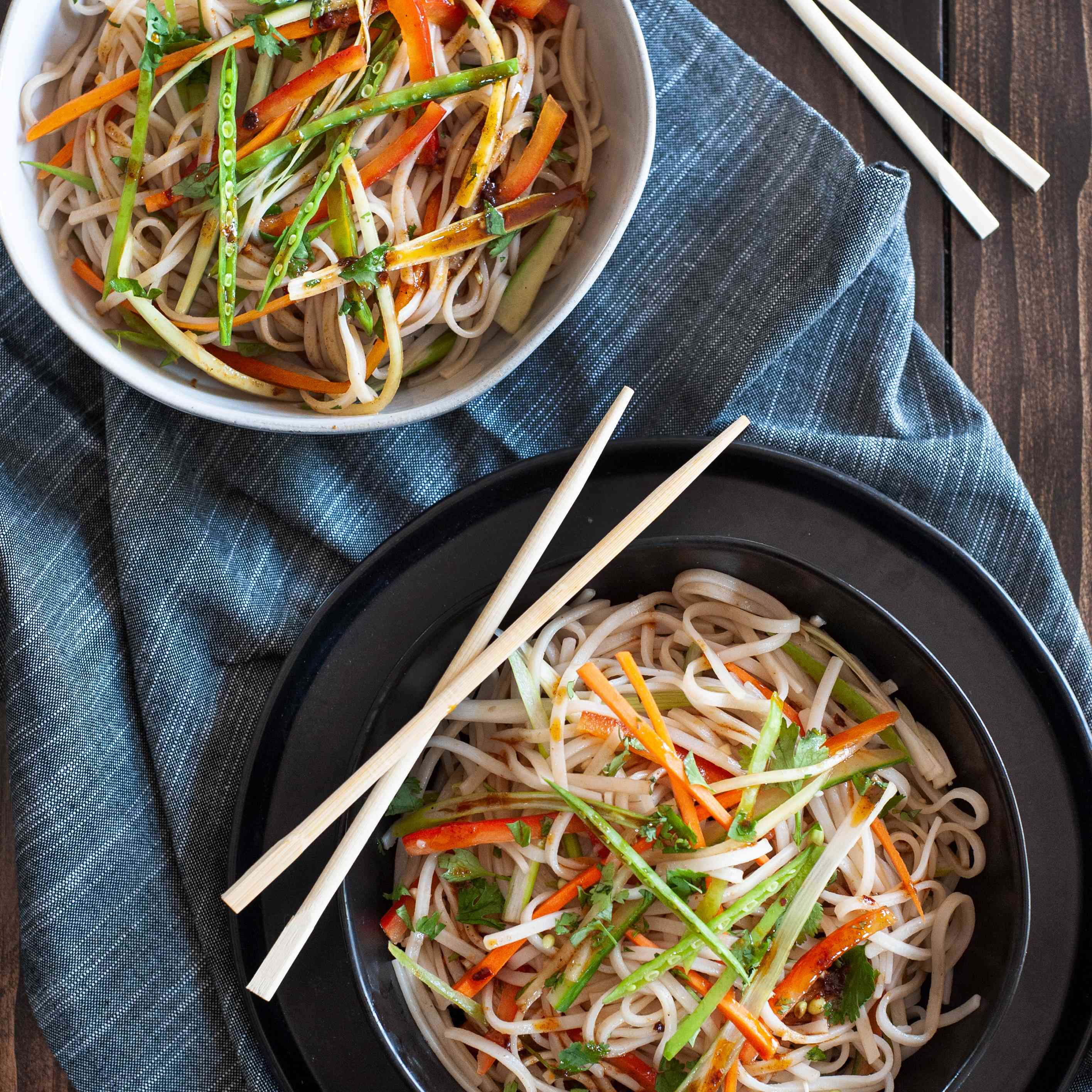 Rice noodle salad with sesame dressing seen overhead in two bowls with chopsticks set next to them.