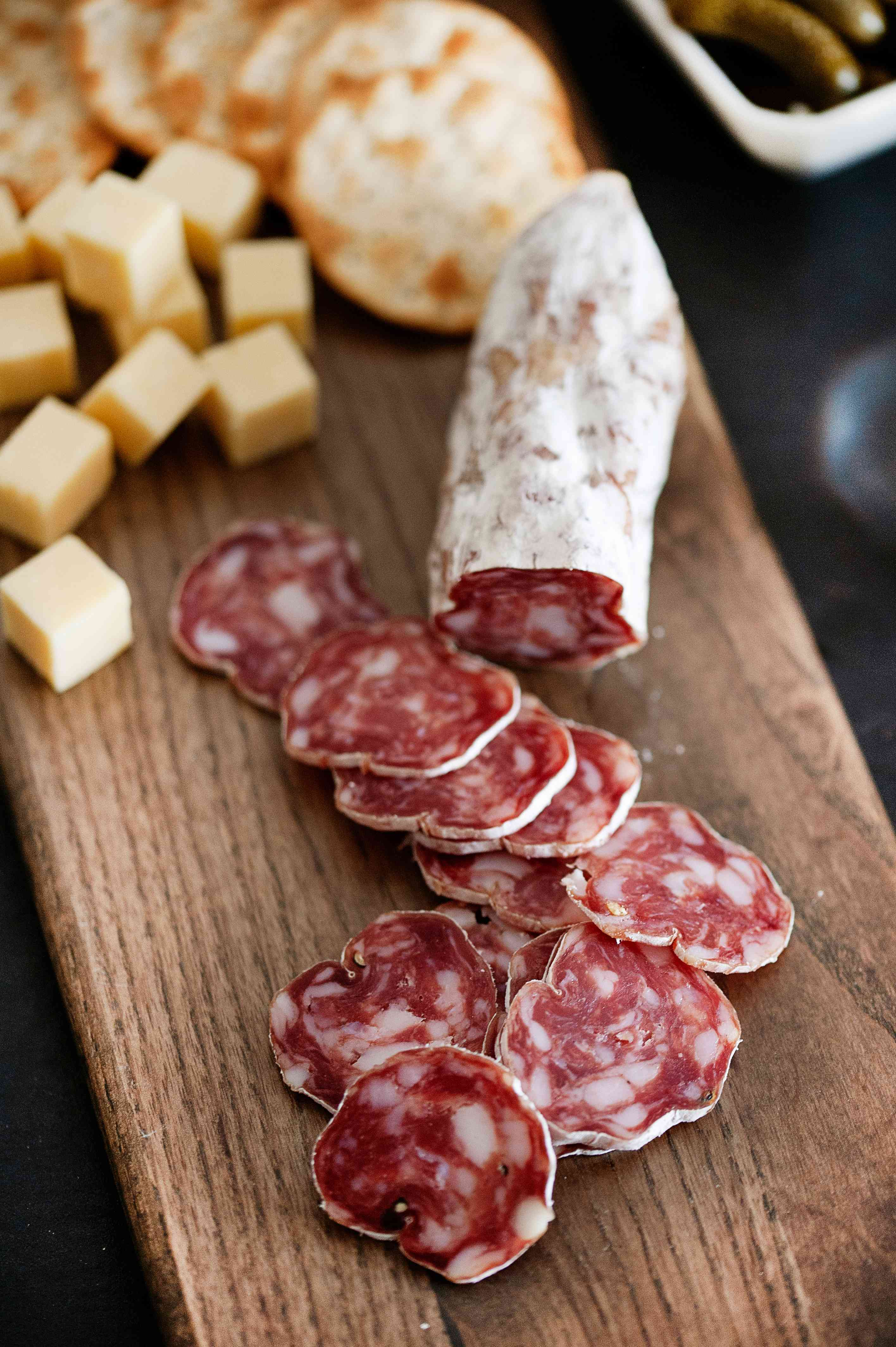 sliced soppressata link and crackers on cutting board