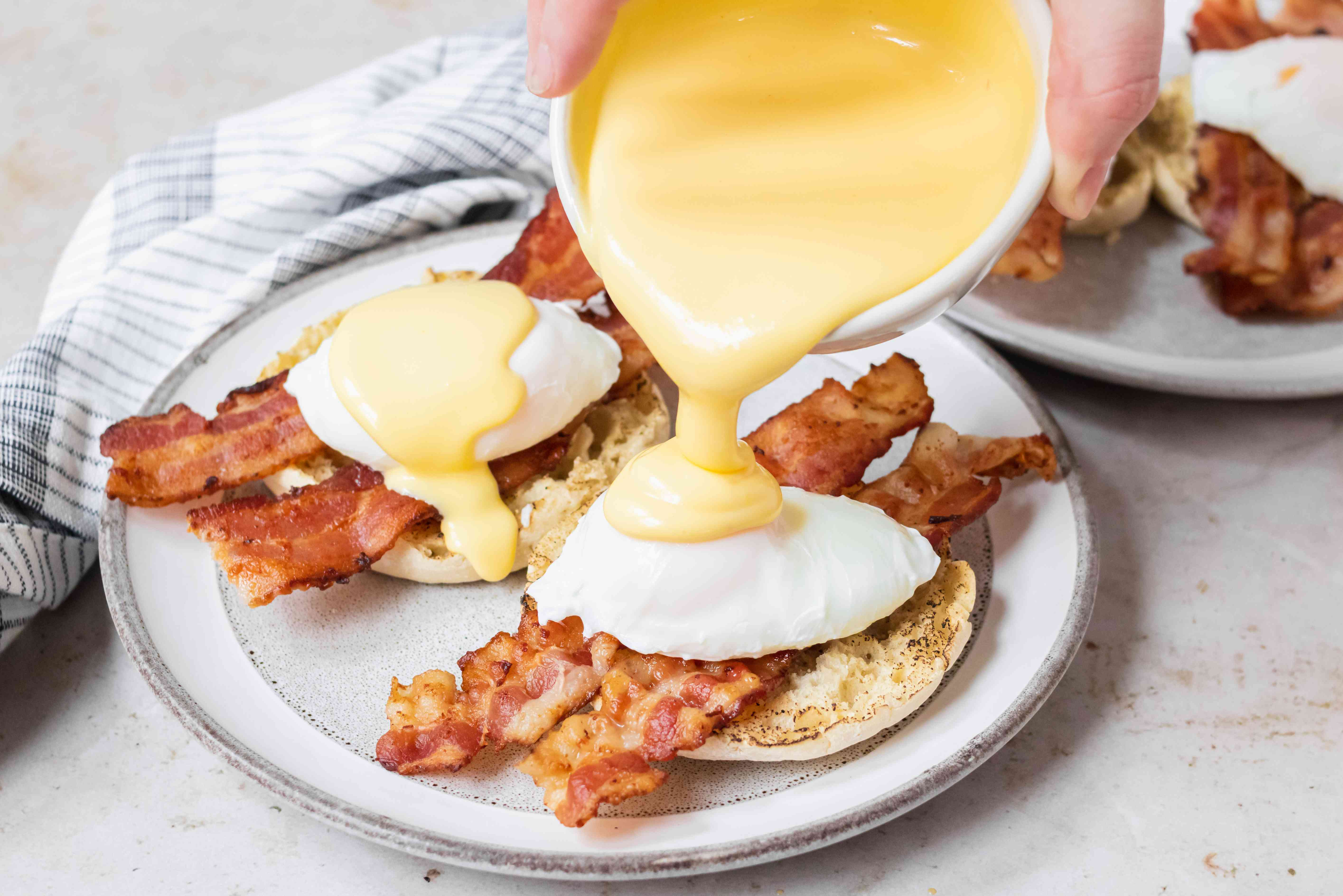 English muffins with bacon, poached egg, and being topped with hollandaise to show how to make eggs benedict.