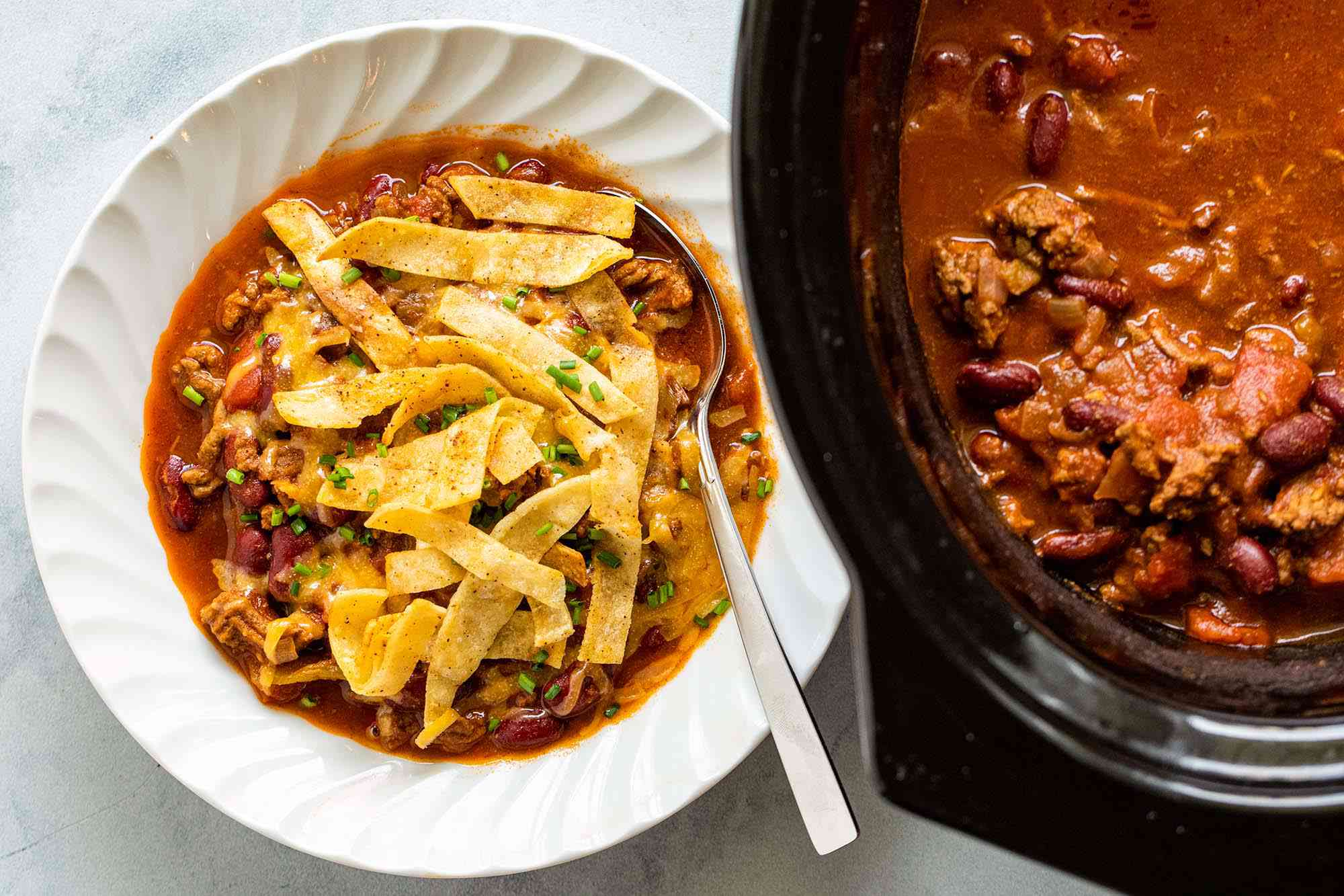Easy Slow Cooker Beef and Bean Chili topped with fried tortilla stips in a white bowl. A crock pot is to the right of the bowl.
