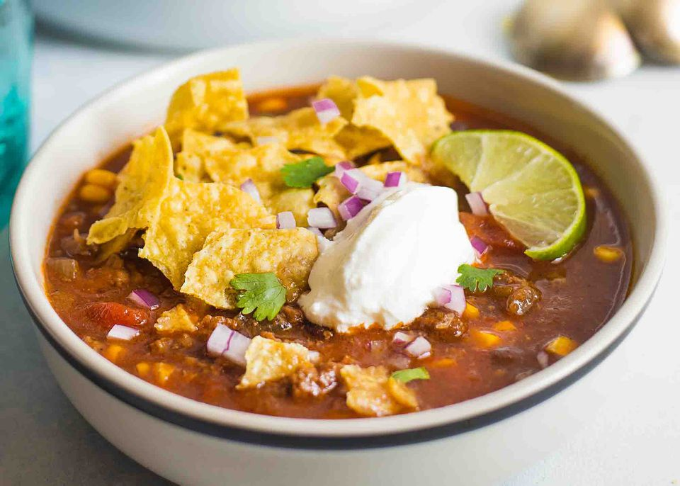 A bowl of crockpot Taco Soup topped with sour cream and chips