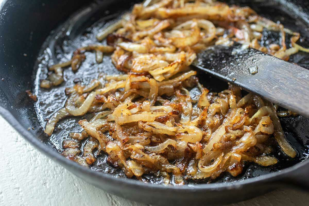 Caramelized onions in a cast iron skillet to make a homemade patty melt.