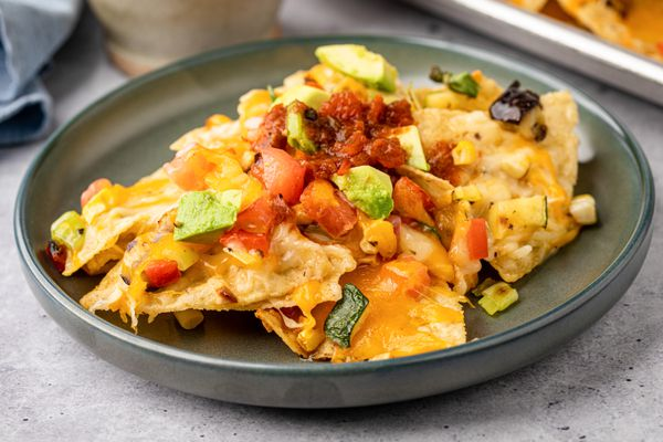 A rimmed plate of grilled eggplant, zucchini, corn, scallion, bell pepper, and tomato nachos.