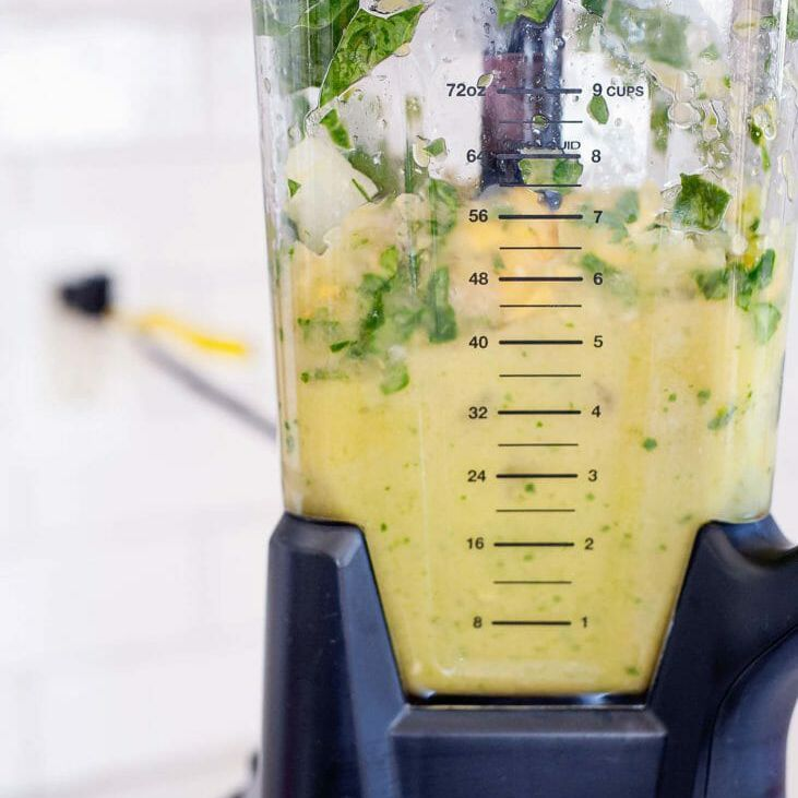 Close up view of a high speed blender jar with spinach and fruit partially processed inside.