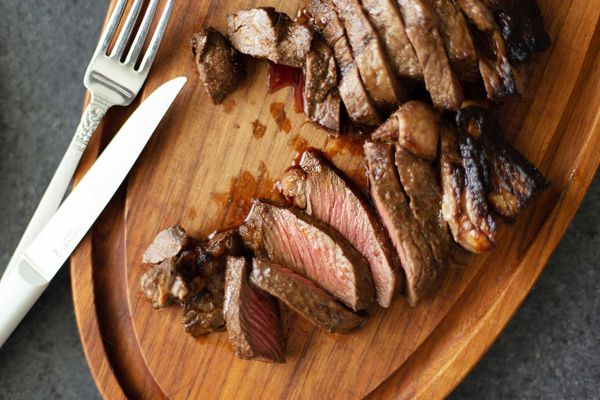 Overhead view of sliced steak cooked in the oven and silverware on a wooden cutting board.